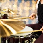 people, musical instruments and entertainment concept - close up of female musician playing drum kit over lights